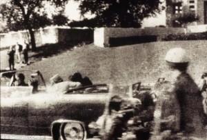 El primer disparo es desviado por un árbol y rebota en el cemento que hiere al testigo James Tague. 3,5 segundos después se produce el segundo disparo que llega a Kennedy por detrás y sale por su garganta, hiriendo también al gobernador de Texas, John Connally. El presidente deja de saludar al público y su esposa tira de él para recostarlo sobre el asiento. El tercer disparo ocurre 8,4 segundos después del primer disparo, justo cuando el auto pasa al frente de la pergola de hormigón. Cuando el tercer disparo impacta de lleno en el occipital derecho de la cabeza de Kennedy, Jackie Kennedy, se abalanza a la parte trasera del auto, donde recoge una sección del cráneo del presidente. Un ciudadano de nombre Abraham Zapruder, que filmaba la comitiva presidencial, logró captar en su película el momento en que Kennedy es alcanzado por los disparos. Esta película es parte del material que la Comisión Warren utilizó en su investigación del asesinato.