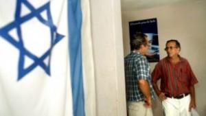 Una bandera israelí cuelga en la pared del centro de la comunidad judía en La Habana, Cuba, donde dos hombres están hablando. Foto de archivo del 01 de agosto de 2004. (Serge Attal / Flash90)