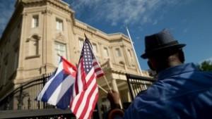 Edwardo Clark, un cubano-estadounidense, sostiene una bandera americana y una bandera cubana mientras celebra fuera de la nueva embajada de Cuba en Washington, 20 de julio de 2015. (AP / Andrew Harnik)