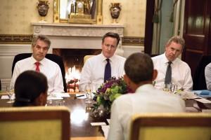 El primer ministro británico, David Cameron, flanqueado por funcionarios del Reino Unido, asiste a la cena en la Casa Blanca en enero de 2015. (Pete Souza / Casa Blanca)