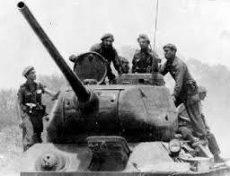 Fidel Castro Ruz, máximo líder de la Revolución cubana acompañado de su escolta personal, compuesta por el Capitán Alfredo Gamonal y el Captan José Obrantes Fernández sobre un tanque T-34 de fabricación rusa en el teatro de operaciones en la Cienaga de Zapata.