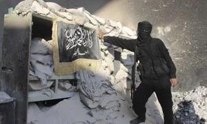 """""""Hay dos guerras en Siria"""", dijo Mustafa Alani, analista del Centro de Investigación del Golfo, una institución con respaldo Saudita: """"Una contra el régimen sirio y otra en contra al-Qaida. Arabia Saudita está luchando a favor de los que luchan en contra el régimen sirio"""". Mientras el jefe de inteligencia saudí, el príncipe Bandar bin Sultan , también está presionando a los EE.UU. a abandonar sus objeciones a suministrar misiles antiaéreos y antitanques a la JAI. Se instó a Jordania para permitir que su territorio sea utilizado como ruta de suministro a la vecina Siria. Foto: Un luchador de Jabhat al-Nusra planta su bandera en un puesto de control en Aleppo. El esfuerzo se centra en Arabia Jaysh al-Islam y excluye a los afiliados de Al Qaeda como Jabhat al-Nusra/ Stringer / Reuters"""