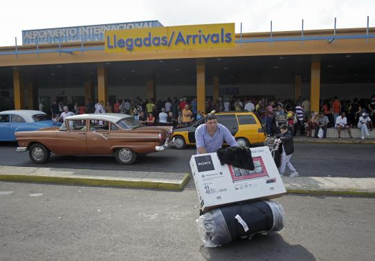A passenger pushes a luggage cart after arriving on a charter flight from Tampa at the airport in Havana